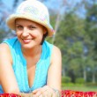 Portrait of young beautiful woman in colorful hat in summer environment — Stock Photo #25968213
