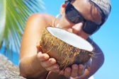 View of a woman opening big coconut in tropical environment — Stock Photo
