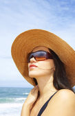 Portrait of young beautiful woman in straw hat and sunglasses — Stock Photo