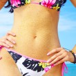 View of nice colorful womans belly covered with sand — Stock Photo #26009451