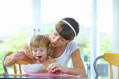 Portrait of young woman feeding her baby daughter — Stock Photo