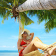 Stock Photo: View of nice woman lounging in hammock in tropical environment