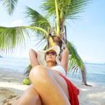 View of nice woman lounging on tropical beach in white panama and bikini — Stock Photo