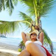 Stock Photo: View of nice woman lounging on tropical beach in white panama and bikini