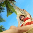 View of nice woman lounging in hammock in tropical environment — Stock Photo #26047349