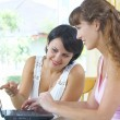 Portrait of two young woman playing with computer — Stockfoto