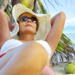 View of nice woman lounging on tropical beach in white panama and bikini — Stock Photo #26047705