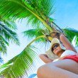 View of nice woman lounging on tropical beach in white panama and bikini — Stock Photo #26054181