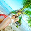 View of nice woman lounging on tropical beach in white panama and bikini — Stock Photo #26054271