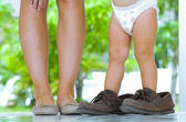 Close up view of baby trying to walk in daddys shoes — Stock Photo