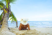 View of nice woman lounging on tropical beach in white panama and bikini — Стоковое фото