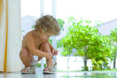 High key portrait of baby trying to put on mamas shoes — Stock Photo
