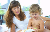 High key portrait of young mother reading a book for her baby — Stock fotografie