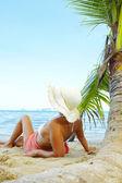Syn på trevlig kvinna på tropisk strand i vit panama och bikini — Stockfoto
