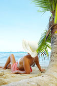 View of nice woman lounging on tropical beach in white panama and bikini — Stok fotoğraf