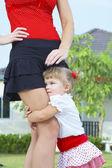 High key portrait of nice baby staying by mamas leg — Stock Photo