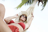 View of nice woman lounging in hammock in tropical environment — Stock Photo