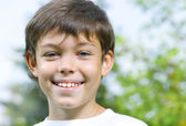 Portrait of happy smiling kid in summer environment — Stock Photo