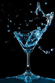 View of glass with Blue Curacao splash on black background — Stock Photo