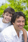 Portrait of young happy father getting busy with his son — Stock Photo