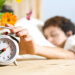 Close up view of table clock and woman sleeping on back — Stock Photo #26128257