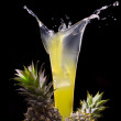 View of fresh pineapple juice splashing out of glass — Stok fotoğraf