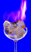 View of cocktail glass filled with burned ice on blue back — Stock Photo