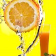 View of piece of orange getting splashed and glass of juice on back — Lizenzfreies Foto