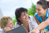 Portrait of happy family getting busy with laptop — Stock Photo