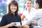 Portrait of young pretty women having coffee break in office environment — Foto Stock