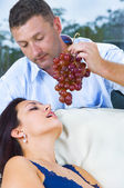 Close up portrait of nice young brunette getting tempted with grape — Stock Photo