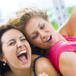 Постер, плакат: Portrait of two young attractive girls having good time
