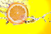 View of piece of orange getting splashed on yellow back — Stock Photo