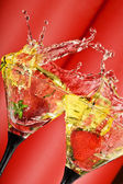 View of martini glass with vermouth and strawberry dropping in — Stock Photo