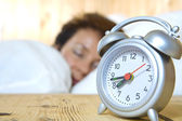 Close up view of table clock and woman sleeping on back — Stock Photo