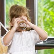 Portrait of little girl having drink in domestic environment — Stock Photo