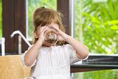 Portrait of little girl having drink in domestic environment — Stock Photo