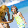Portrait of young woman with her daughter on beach — Stockfoto