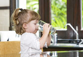 Portrait of little girl having drink in domestic environment — Stockfoto