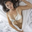 Portrait of young beautiful woman on white sheet — Stockfoto