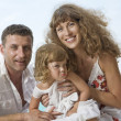Portrait of young family having fun on the beach — Stock Photo