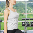 Portrait of young woman  getting busy in gym — Stock Photo