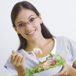 Portrait of young beautiful brunette with vegetable salad — Stock Photo