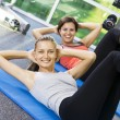 Portrait of young nice women getting busy in gym — Stock Photo