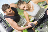 Portrait of young nice couple getting busy in gym — Stock Photo