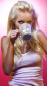 Portrait of young nice woman with cup on pink back — Stock Photo