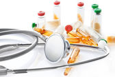 Close up view of grey stethoscope and ampoules — Stock Photo