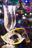 Two glasses of champagne and venetian mask — Stock Photo