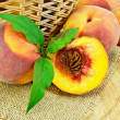 Peaches with leaves and a basket on board - Stok fotoğraf