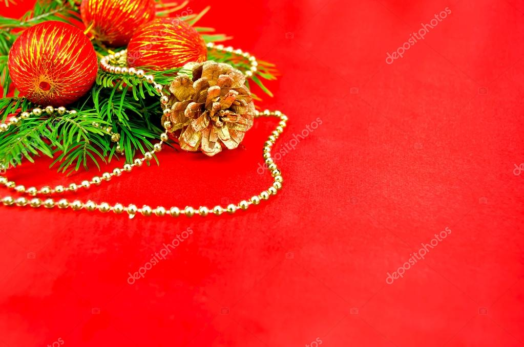 The fir branches, three red spheres, one golden cone, golden ornaments against red silk — Stock Photo #14893557